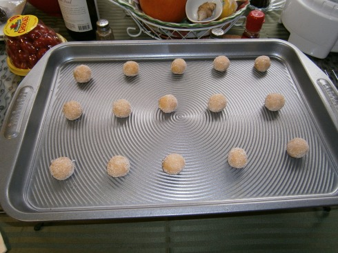 Pinch off pieces of dough from the doughball and roll them into balls. Roll them into some sugar to coat, and then place on the baking sheet. No need to grease or anything, they pop right off after coming out of the oven.