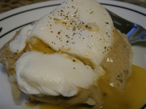 Poached egg with mustard-cream sauce on an English muffin.