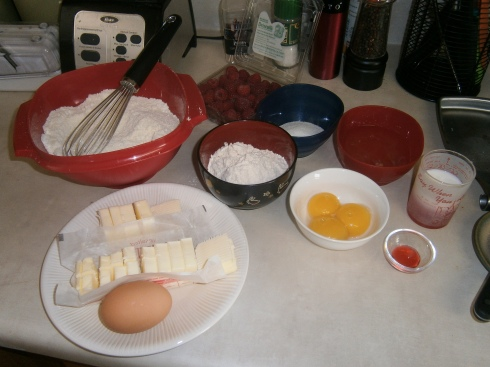 A whole counter-full of ingredients: almond flour and powdered sugar sifted together, raspberries, sugar, egg whites and yolks, milk and rose syrup, raspberry extract, flour, an egg, and lots of butter.