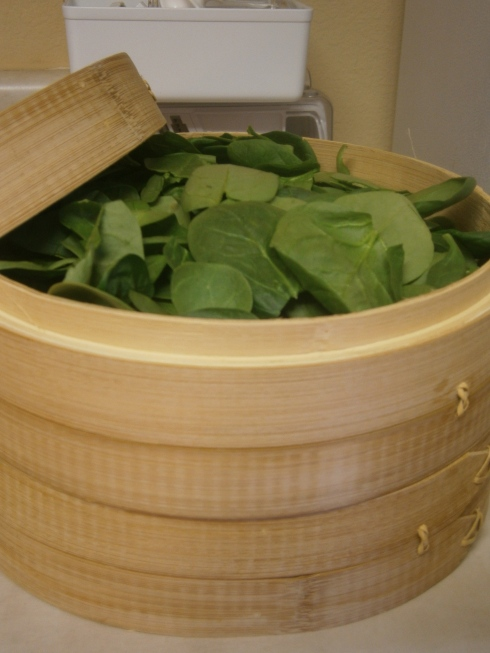 All ten ounces of spinach stuffed into the two levels of the bamboo steamer.